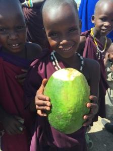 Maasai child showing me a wild papaya fruit